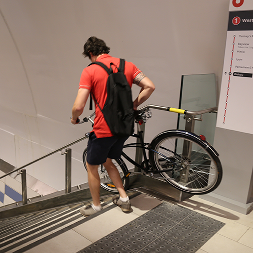 Man placing his bicycle in a runnel to go down the staircase.