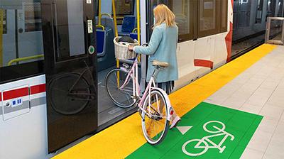 Usagère qui monte à bord de l'O-Train avec son vélo.