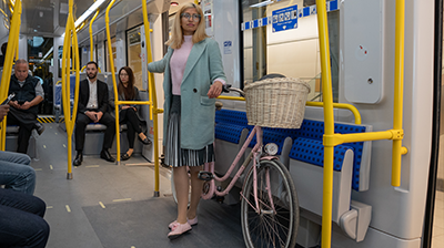 Customer holding her bicycle as she rides in the Cooperative Seating area of the O-Train.