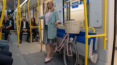 Usagère qui tient son vélo dans la section des sièges à partager de l'O-Train.