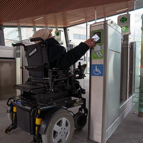 Customer with a mobility device tapping his smart card at an accessible fare gate.