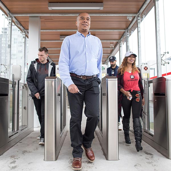 Customers walking through fare gates at an O-Train station.