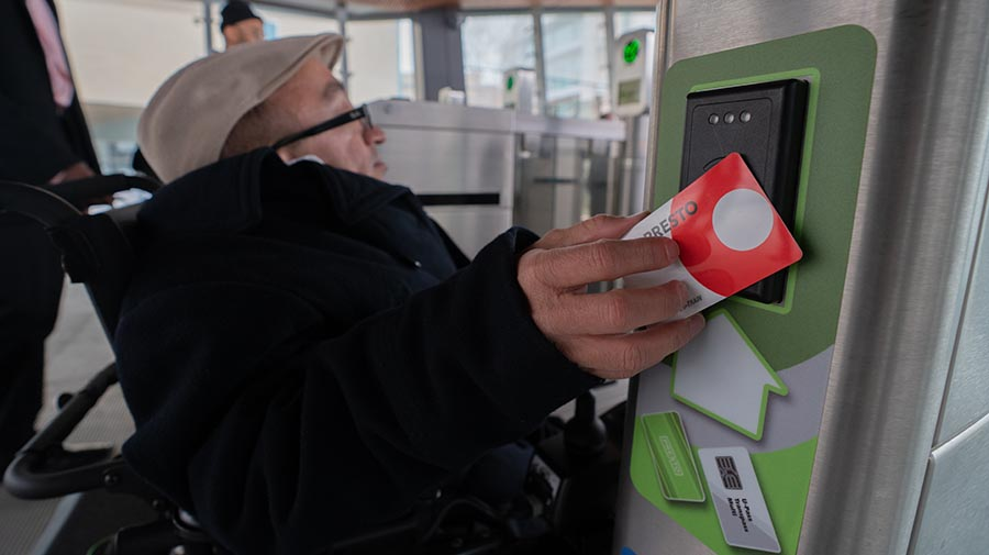 Passenger tapping his Presto card at an accessible fare gate.