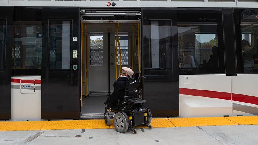 Passenger with a wheelchair boarding O-Train Line 1.