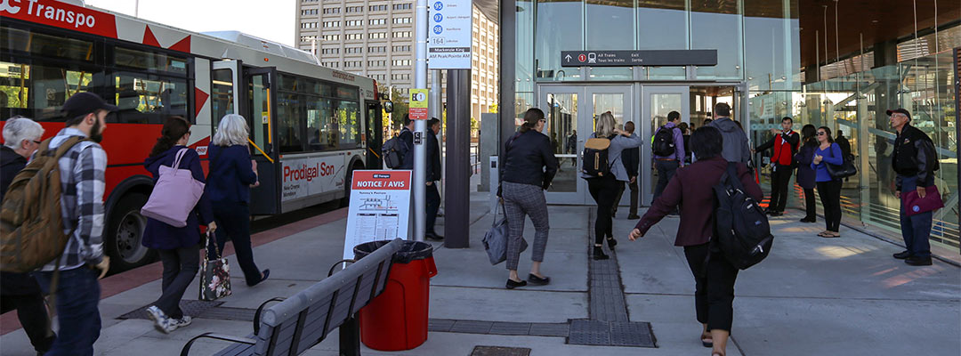 Passengers transferring by bus to O-Train Line 1 at Tunney's Pasture Station.