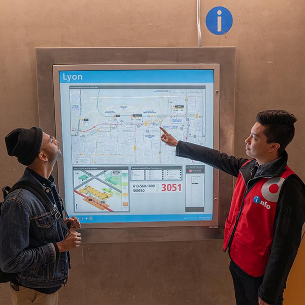 O-Train Ambassador showing a passenger the transit system map.