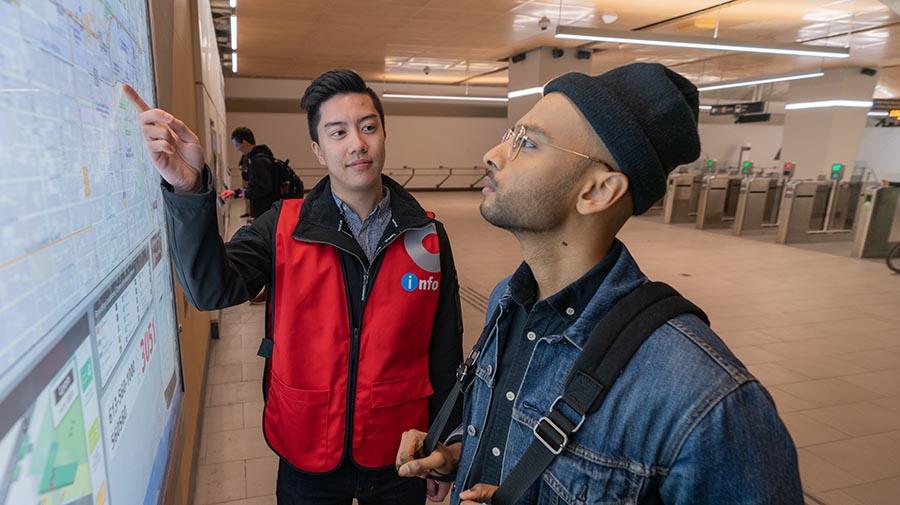 Ambassadeur de l'O-Train indiquant un trajet sur une carte murale.