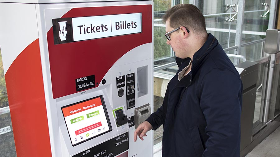 Homme utilisant une distributrice de billets.