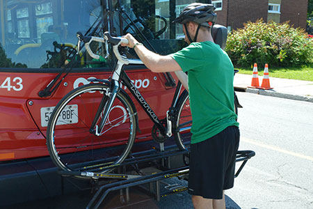 A man places his bike on the rack on the front of a bus