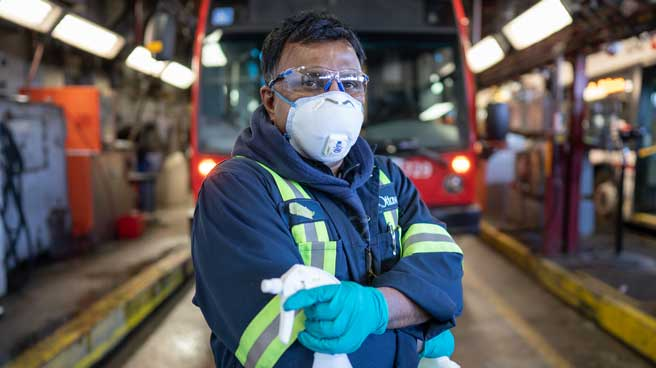 OC Transpo employee posing in front of a bus wearing goggles, a face mask, and gloves and holding cleaning supplies.