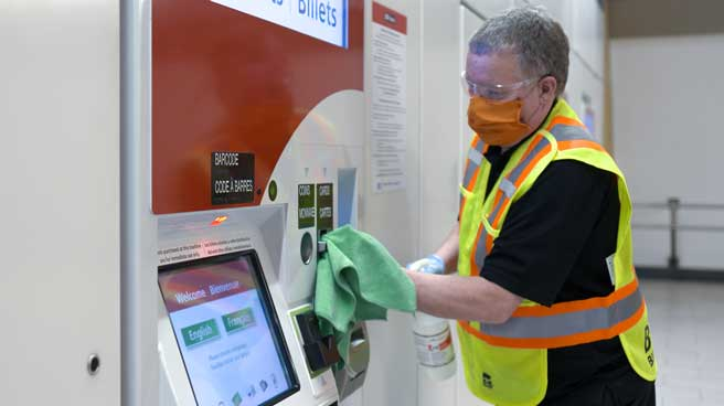 Attendant cleaning the ticket machine inside station