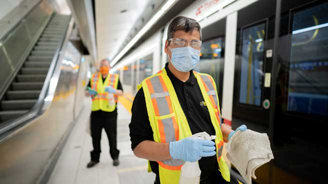 Two attendants inside the station with cleaning equipment, both wearing safety vests and masks