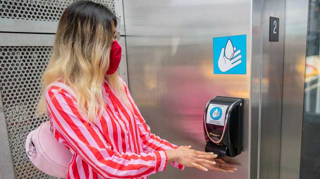 Woman using the hand sanitizer dispenser