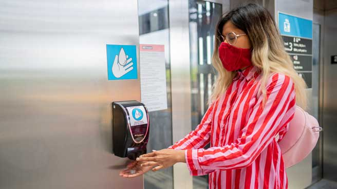 Woman wearing a mask using a hand sanitizer dispenser at a Line 1 station.