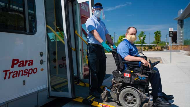 Masked Para Transpo customer exits a Para Transpo vehicle with the assistance of a Para Transpo Operator wearing a surgical mask, face shields, and gloves.