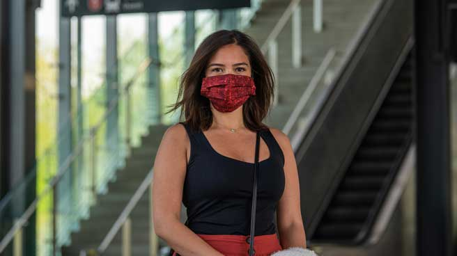 Woman wearing a cloth face mask inside a Line 1 station.