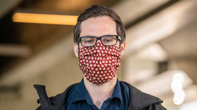 Man with glasses wearing a mask inside a Line 1 station.