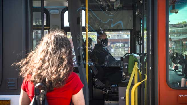 A woman boarding the front door of a bus, the operator in the background behind protective shield