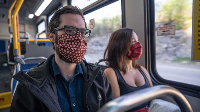 Two passengers sitting on a bus, side by side, wearing masks
