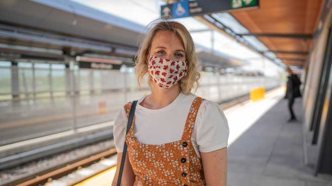 Woman on the station platform, wearing a mask