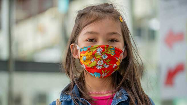 Young girl wearing a cloth face mask inside a Line 1 station.