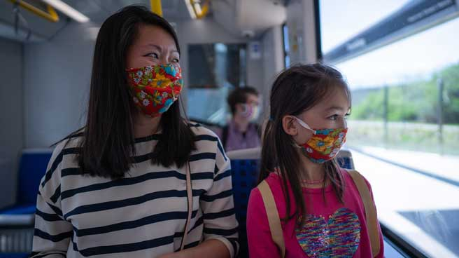 Mother and daughter riding the train, both wearing mask