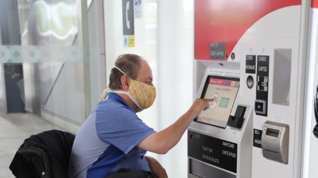 Customer wearing mask using the ticketing machine.