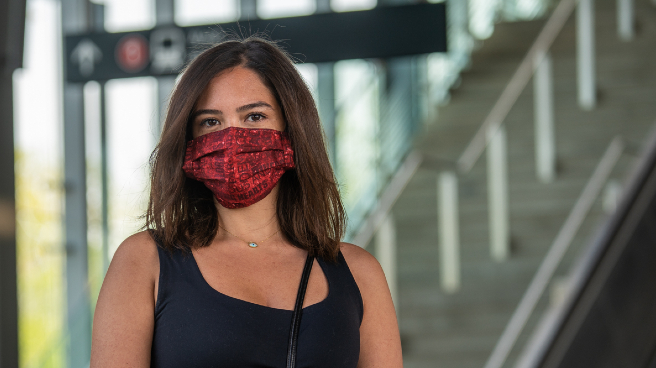 Woman wearing a cloth mask, station in background