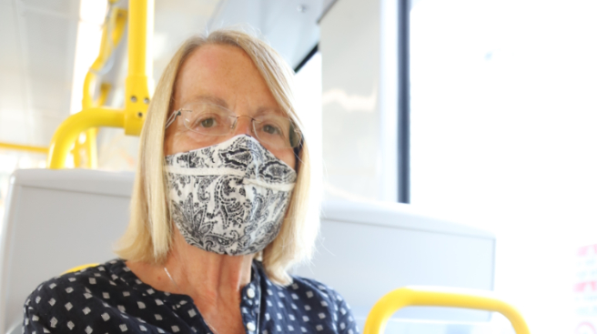 An older woman riding transit wearing a mask