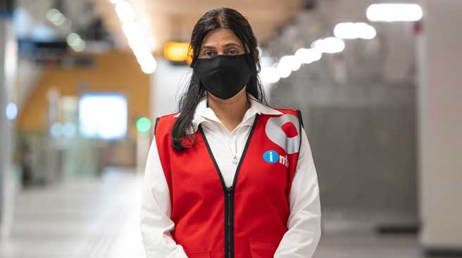 Female O-Train Ambassador, wearing a red-vest uniform and mask