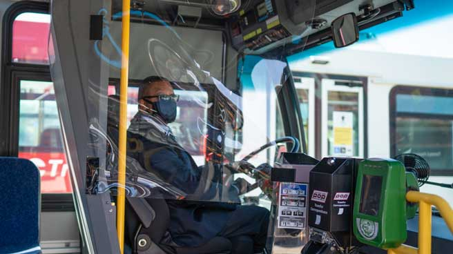 OC Transpo Operator seated at the wheel of a bus wearing a cloth face mask. The Operator area is protected by a soft shield made of clear plastic.