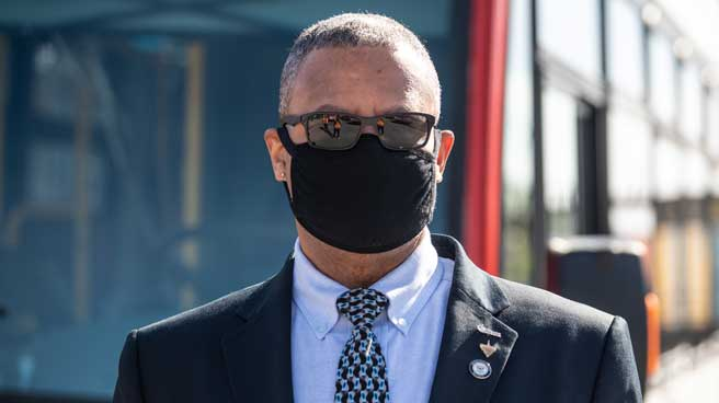 Operator wearing a cloth face mask in front of a bus.
