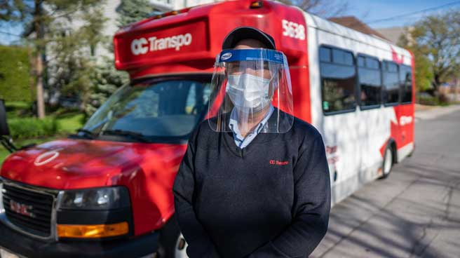 Para Transpo Operator posing in front of a Para Transpo vehicle while wearing a surgical mask and face shield.