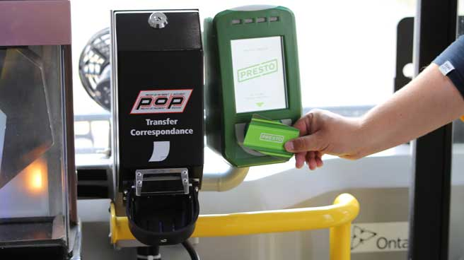 Customer tapping his Presto card as he boards at the front of the bus.