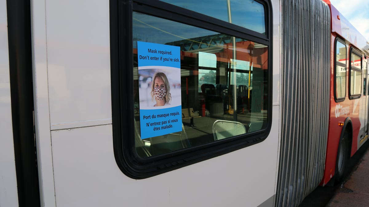 Sign at the back door of a bus featuring a masked transit rider accompanied by the text: Mask required. Don't enter if you're sick.
