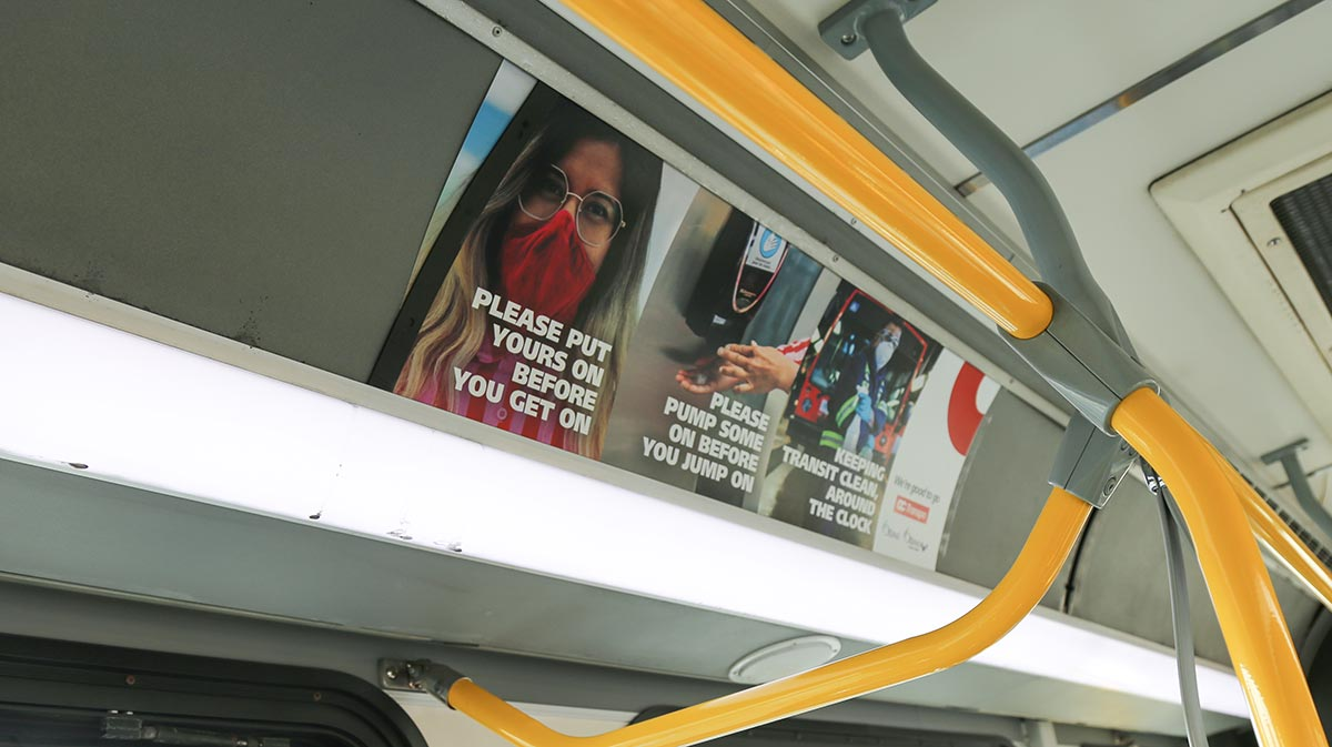 Signage related to mask requirements and other protective safety measures displayed inside of a bus.