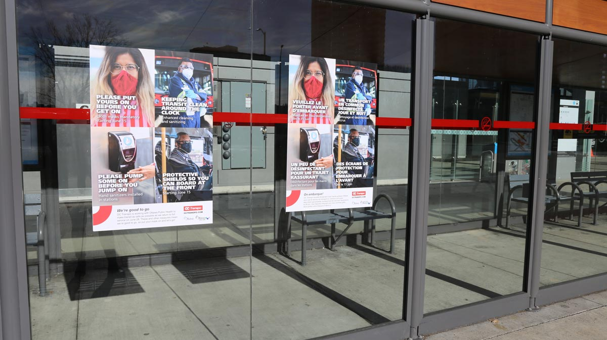 Posters related to mask requirements and other protective safety measures displayed at a bus shelter.