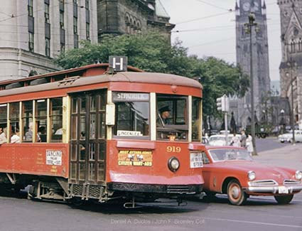 Streetcar 919 travelling through downtown with Sparks Street and Parliament buildings in the background c. 1954. Daniel A. Duclos / John F. Bromley Collection