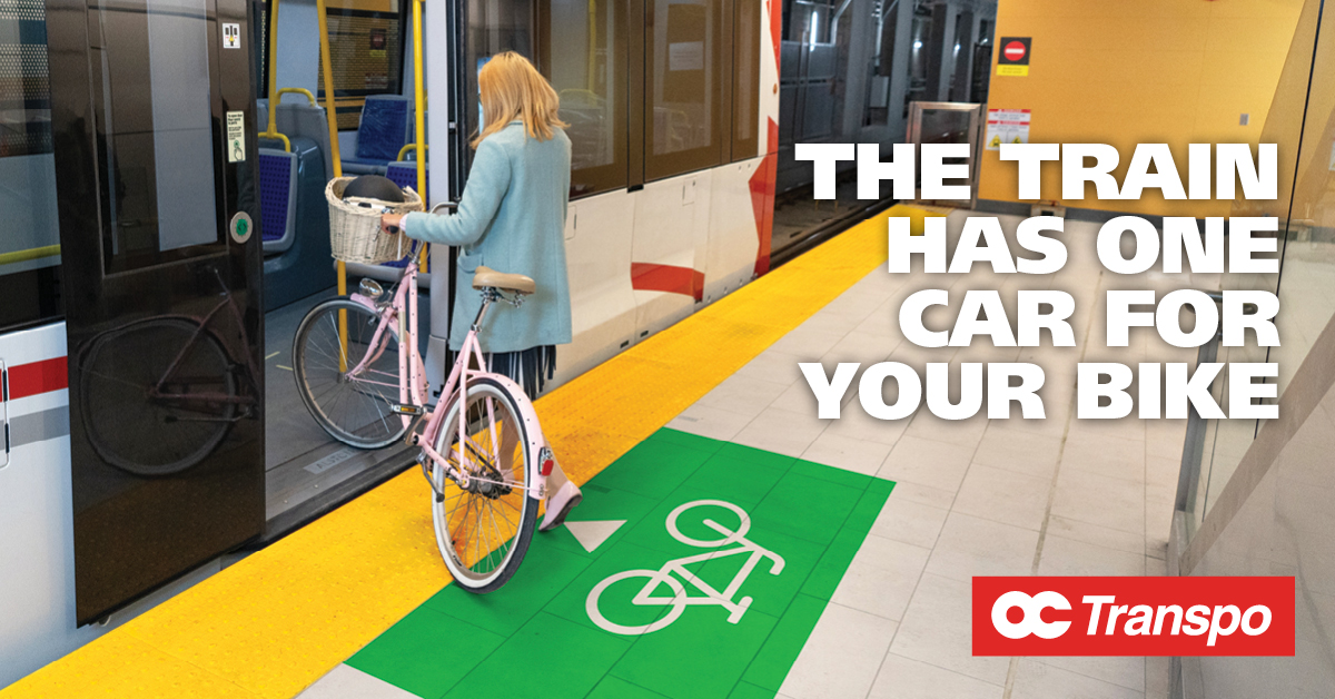 Woman boarding the train with her bike at door marked with bicycle symbol. Image text: The train has one car for your bike. Always board by the door at the front of the train on O-Train Line 1.