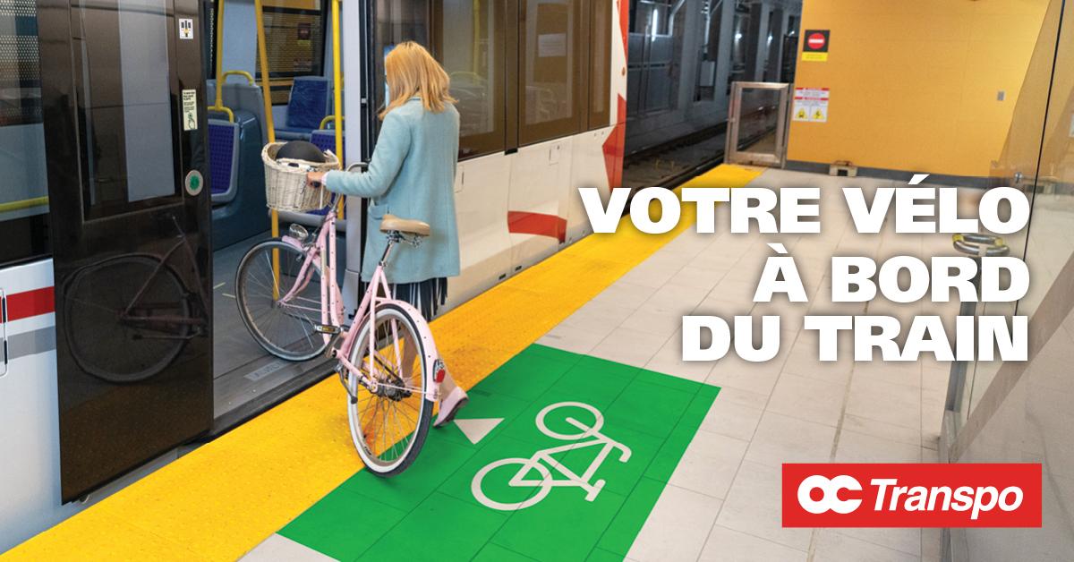 Une femme embarque sa bicyclette à bord du train par la porte identifiée du symbole de vélo. Texte sur l'image : Votre vélo à bord du train. Entrez toujours par la porte de la première voiture de la Ligne 1 de l'O-Train.