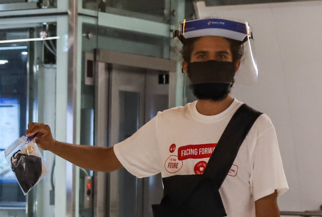 Volunteer wearing a mask and PPE, handing out masks