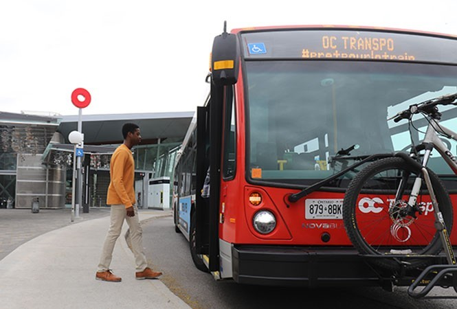 Passenger boarding a bus at a Line 1 station.