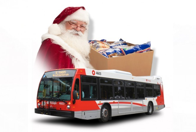Santa holding a box of food donations with a bus