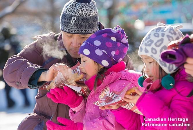 Péchés mignons du Bal de neige! Une famille mange des queues de castor.